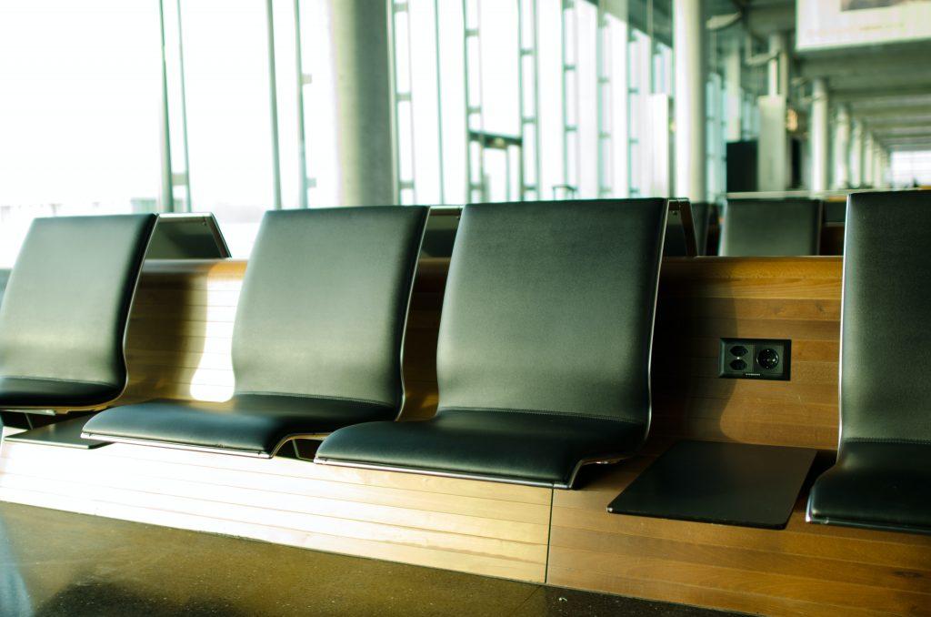 Na imagem há a representação de uma sala de check-in em aeroporto, com bancos em couro preto sobre uma estrutura de madeira.
