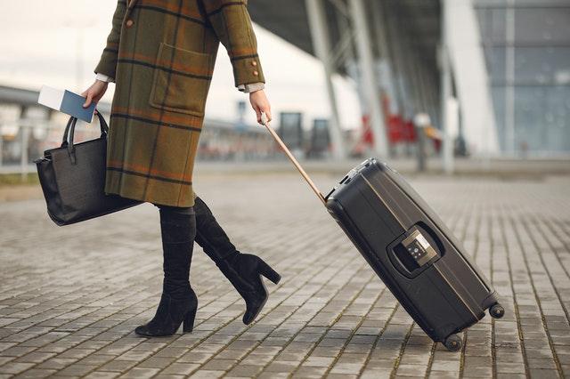 mulher de casaco longo xadrez, marroom com linhas pretas e laranjas, carregando mala de rodinhas em um suposto aeroporto.