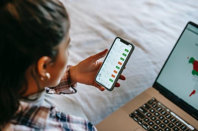 Visão da lateral de uma pessoa com um celula na mão e um notebook no colo chacando suas milhas no app.