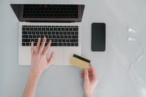 Na imagem há um celular, um fone de ouvido e um notebook apoiados sobre uma bancada, sendo que há uma pessoa mexendo com a mão esquerda no notebook e com a mão direita segurando um cartão.