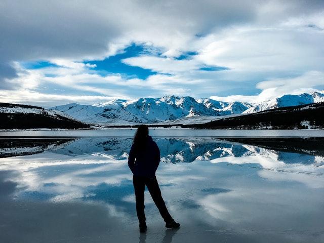 Pessoa parada de costas em frente a uma paisagem espelhada com céu azul e com nuvens, montanhas nas laterais e ao fundo.
