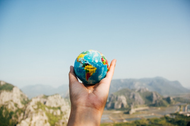 Em foco: mão segurando globo terrestre pequeno, em frente a uma paisagem com um horizonte montanhoso e com bstante verde.