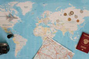 Há um mapa do mundo aberto com algumas moedas e um avião de brinquedo na parte superior, enquanto na parte inferior há uma câmera, passaporte e um mapa fechado.