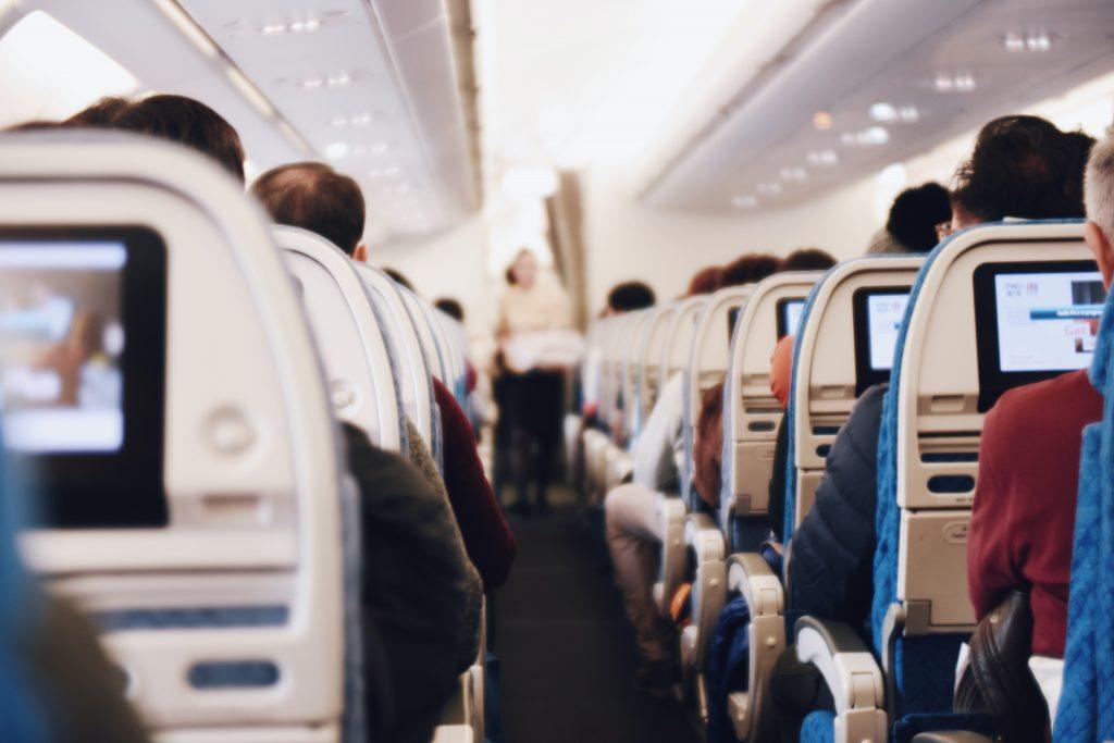 Na imagem há um corredor de um avião, com indivíduos acomodados em seus assentos