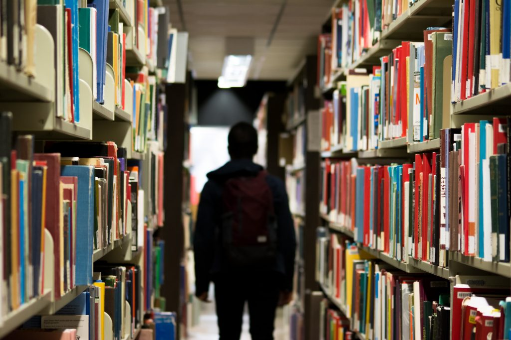 Na imagem há uma pessoa em um corredor de uma biblioteca, onde à sua esquerda e direita há prateleiras com diversos livros alocados.