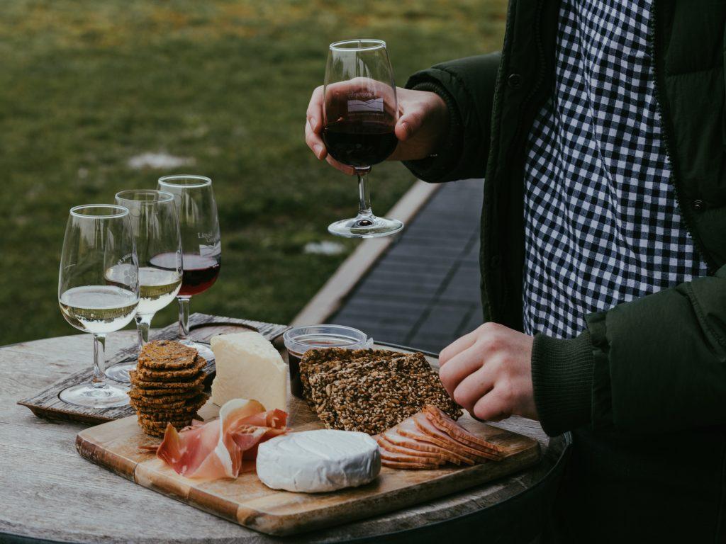 Imagem de uma pessoa branca de camisa quadriculada azul e preta com um casaco verde grosso segurando uma taça de vinho transparente. Na frente da pessoa temos uma mesa onde estão apoiadas mais taças com vinhos distintos e uma bandeja com queijos, pães e salames.
