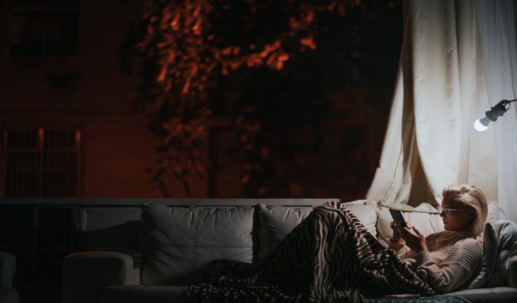 Na imagem há uma mulher deitada em um sofá utilizando um dispositivo de leitura com um abajur ligado.