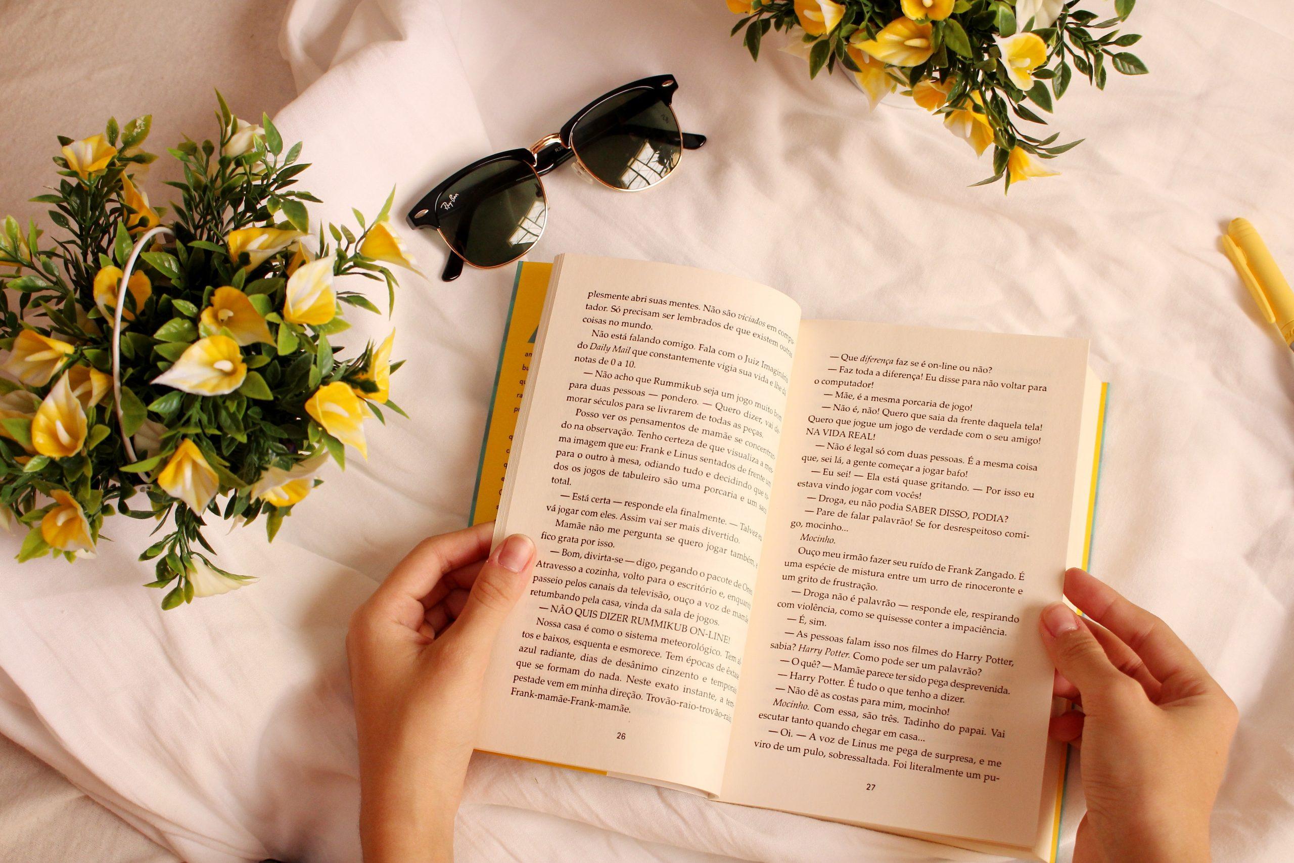 Na imagem há uma pessoa segurando um livro com as duas mãos sobre uma superfície branca. Próximo ao livro há dois arranjos de flores amarelas e um óculos de sol.