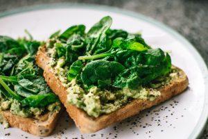 Na figura há duas fatias de pão com um patê de abacate com temperos e ervas sobre um prato branco.