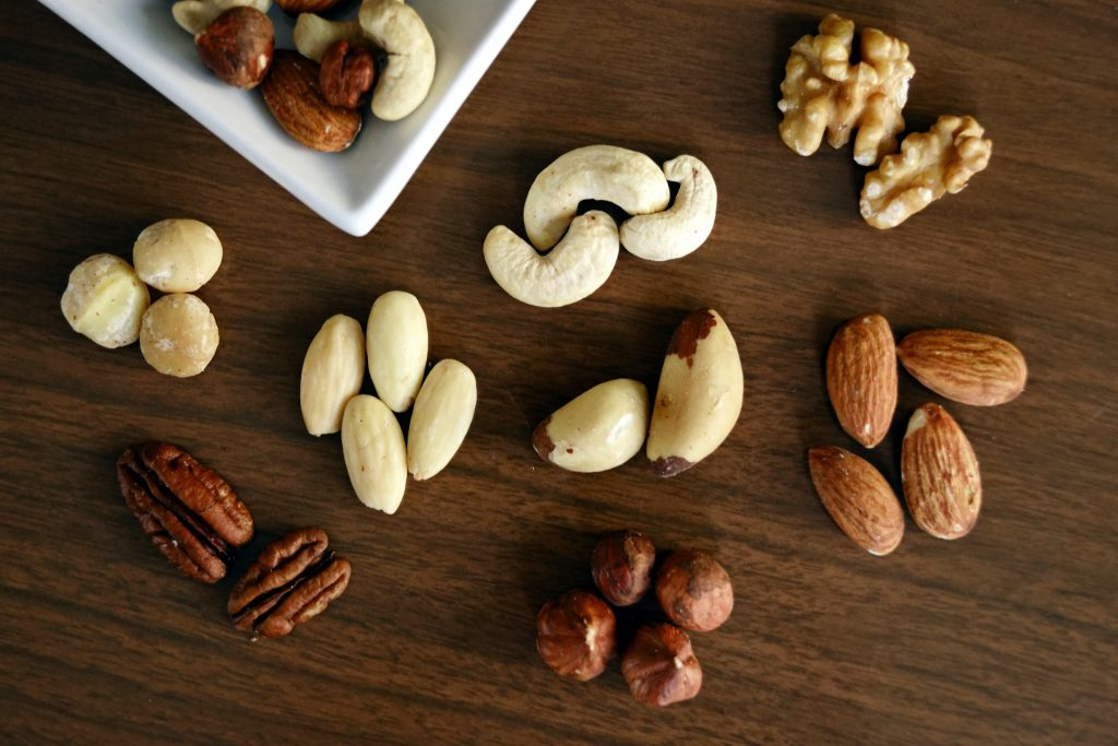 Na imagem há opções de castanhas e frutas secas sobre uma superfície de madeira.