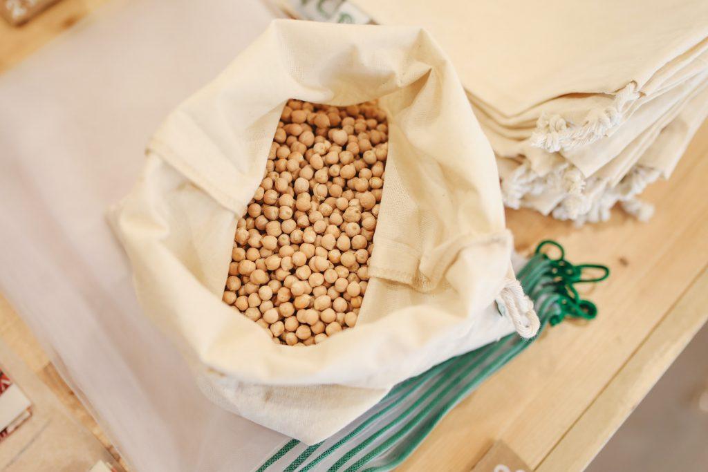 Na imagem há um saco de tecido branco, que está cheio de grão de bico sobre uma superfície de madeira.