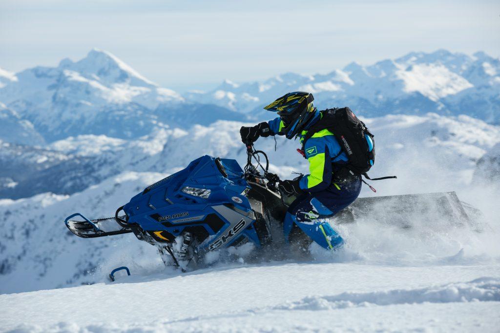 Na imagem há uma pessoa praticando esporte na neve. Está pessoa está utilizando equipamentos de segurança específicos para ambientes de frio intenso e está sobre uma moto de neve, ao fundo há a representação de um local montanhoso coberto de neve.