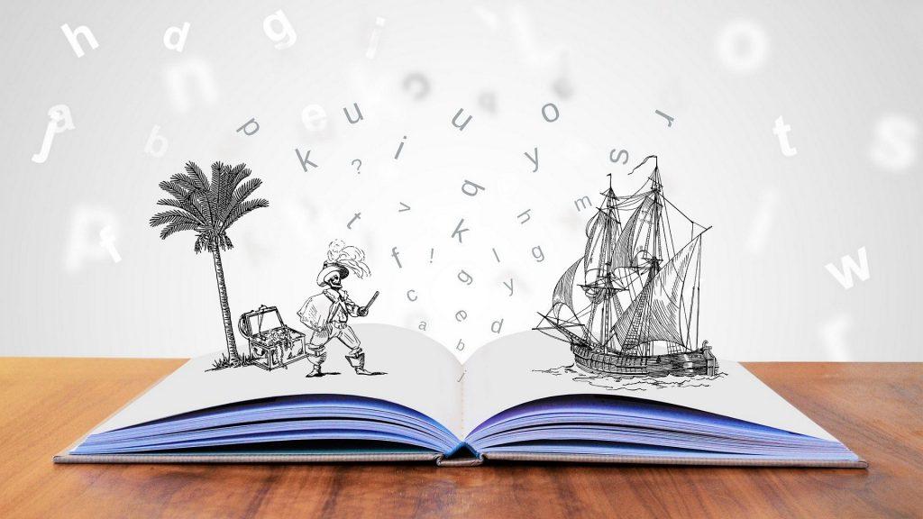 Na imagem há um livro com as folhas em branco aberto sobre uma superfície de madeira, onde há a ilustração de letras saindo do livro, com um pirata e um navio.