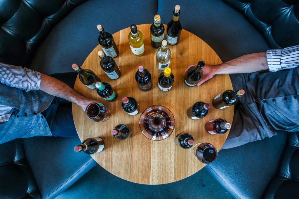 Imagem com vista superior de dois homens brancos sentados em em volta de uma mesa redonda de madeira. Em cima da mesa, existem várias garrafas de vinhos dos mais variados tipos.