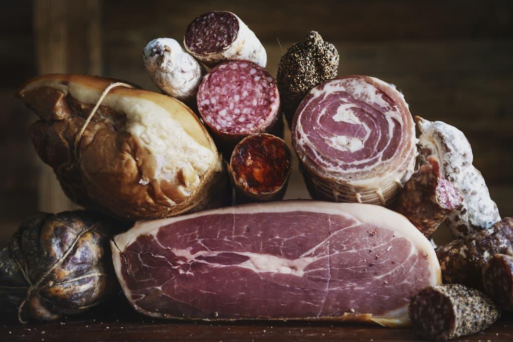 Na imagem vemos diversas peças de alimentos da charcutaria, entre eles estão salames e presuntos. Todos colocados empilhados em cima de uma mesa de madeira escura.