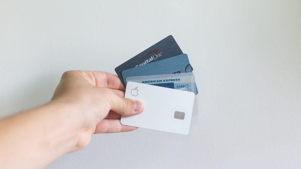 Na imagem há uma pessoa caucasiana segurando três cartões de diferentes bandeiras do mercado financeiro.