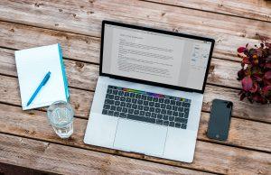 Na imagem há um notebook, um smartphone, um copo de água, uma caderneta e uma caneca sobre uma superfície de madeira.