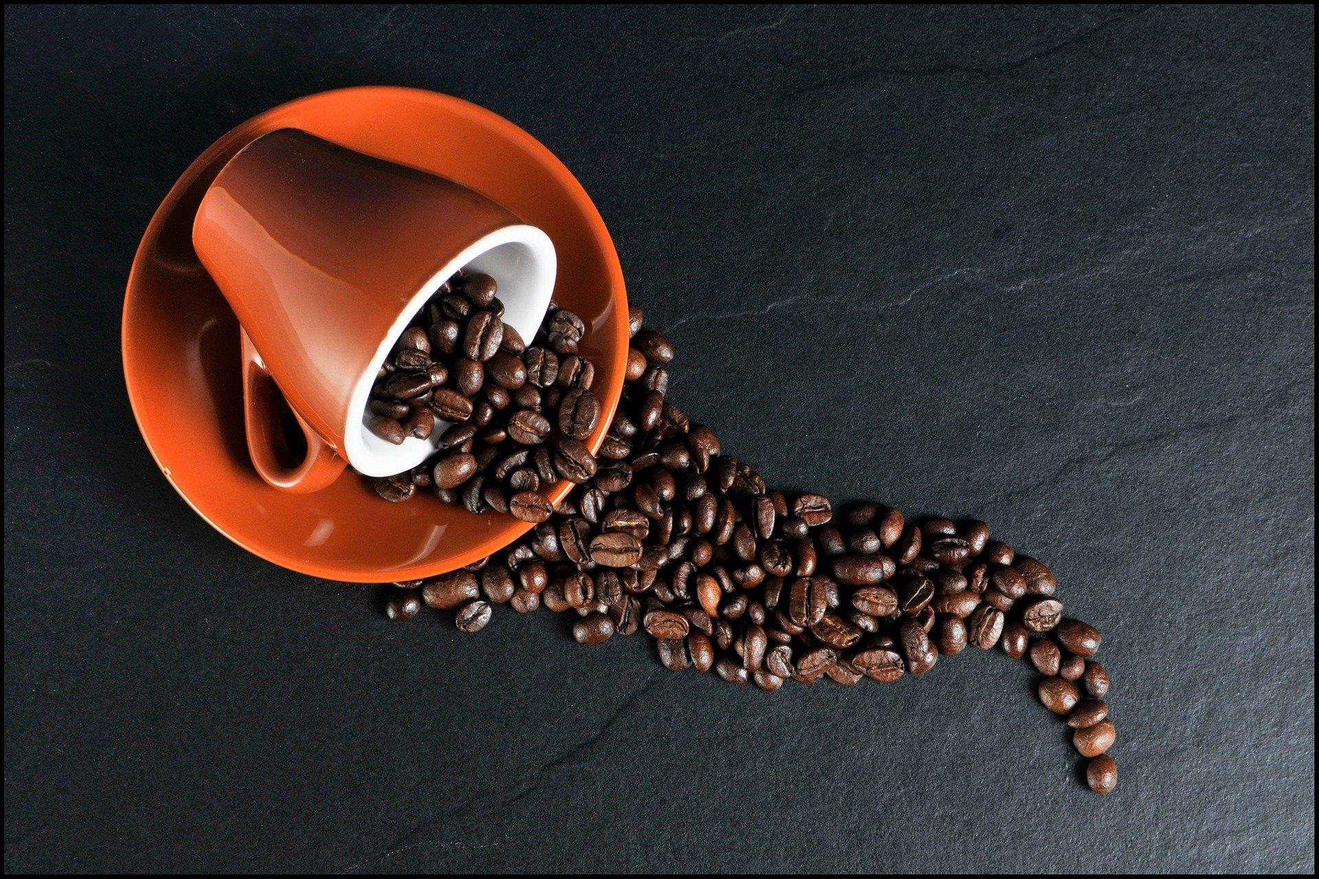 Na imagem há uma xícara deitada sobre o pires com grãos de café esparramando sobre o pires e uma bancada de granito.