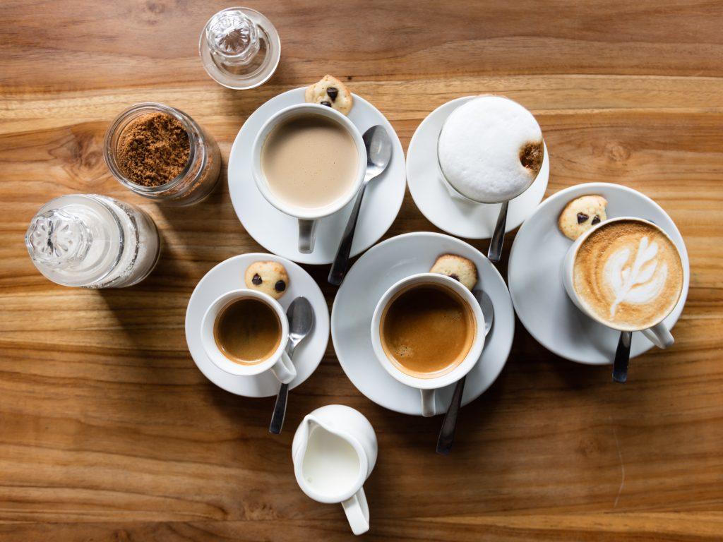 Na imagem há cinco xícaras sendo que cada uma está sobre um pires e com uma colher de café ao lado. Há também uma leiteira com leite e recipientes com açúcar mascavo e outro com açúcar cristal. As xícaras contém diferentes tipos de café.