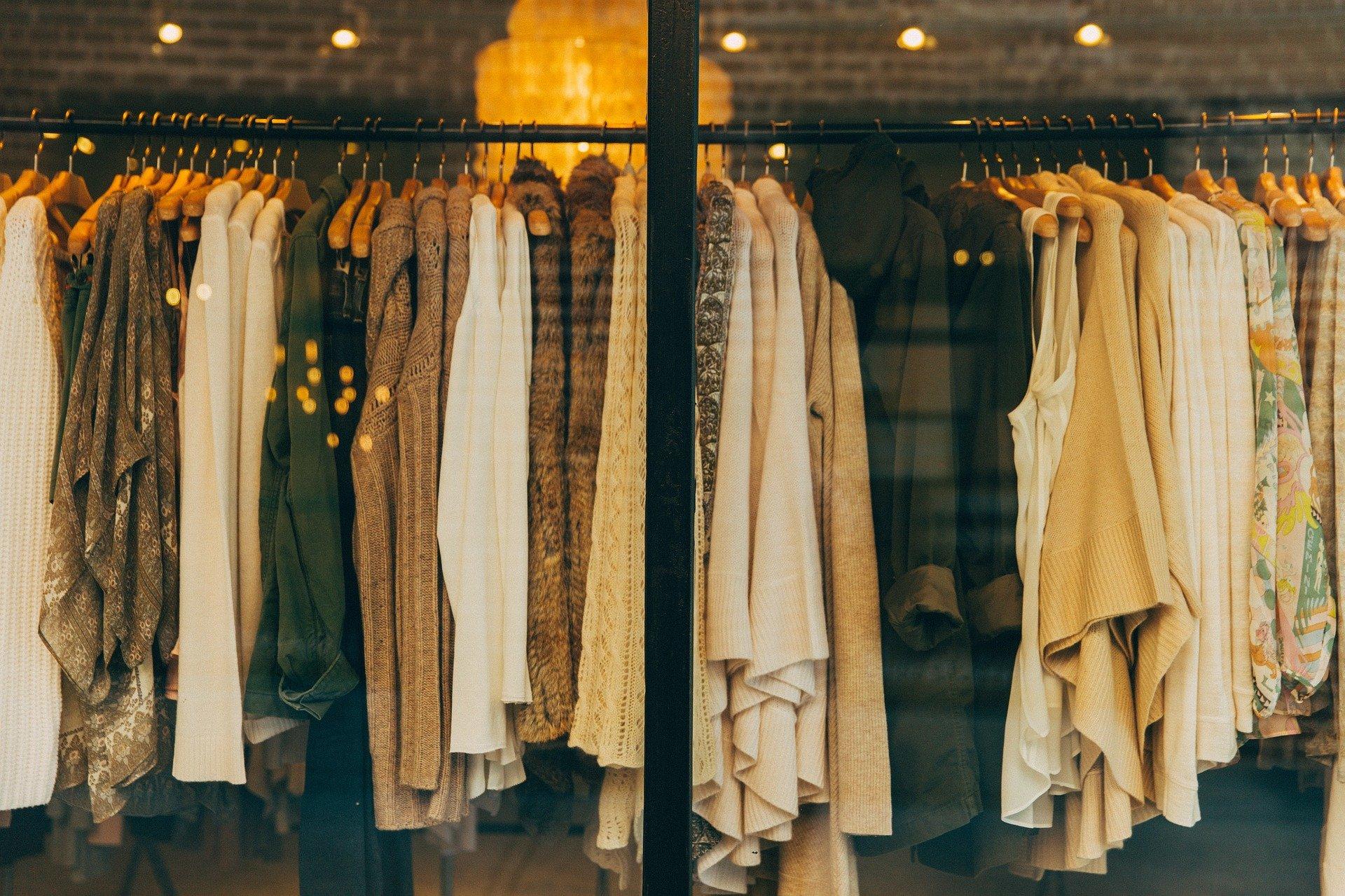 Na imagem há uma vitrine com casacos em cabides em uma arara. As estampas dos casacos são de cores diferentes e com diferentes formas