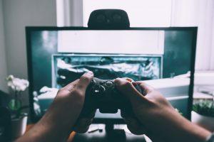 Na imagem há uma pessoa segurando um controle joystick com as duas mãos em frente à uma tela de computador com a imagem de um jogo.