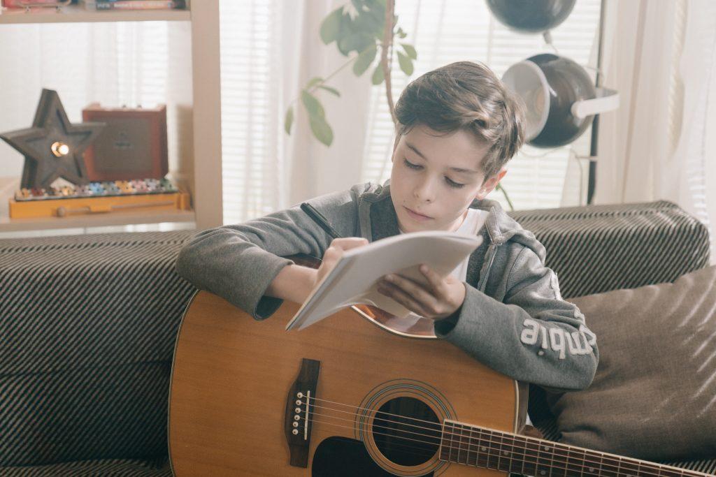 Na imagem há uma criança caucasiana sentada em um sofá, escrevendo com uma caneta em um caderno e com um violão sobre as suas pernas.