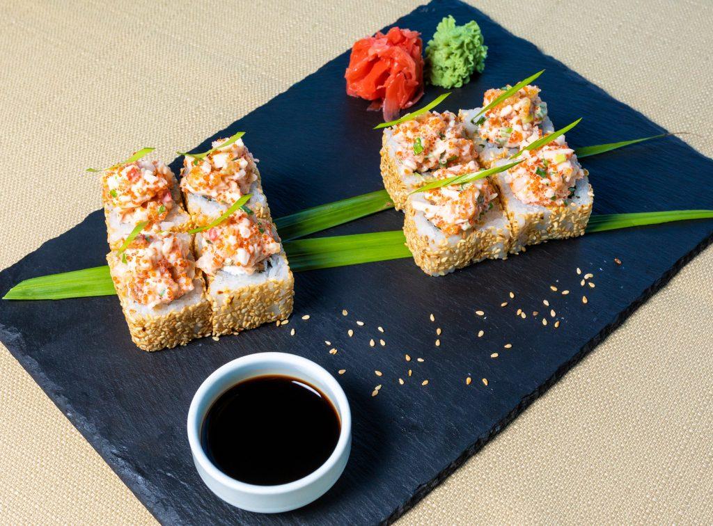 Na imagem há um prato retangular com oito tempurá e uma cumbuca com shoyo.