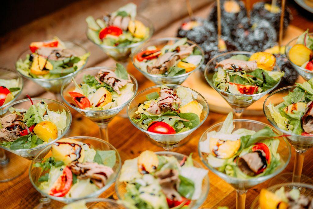 Na imagem há uma mesa com várias taças com um mix de salada.