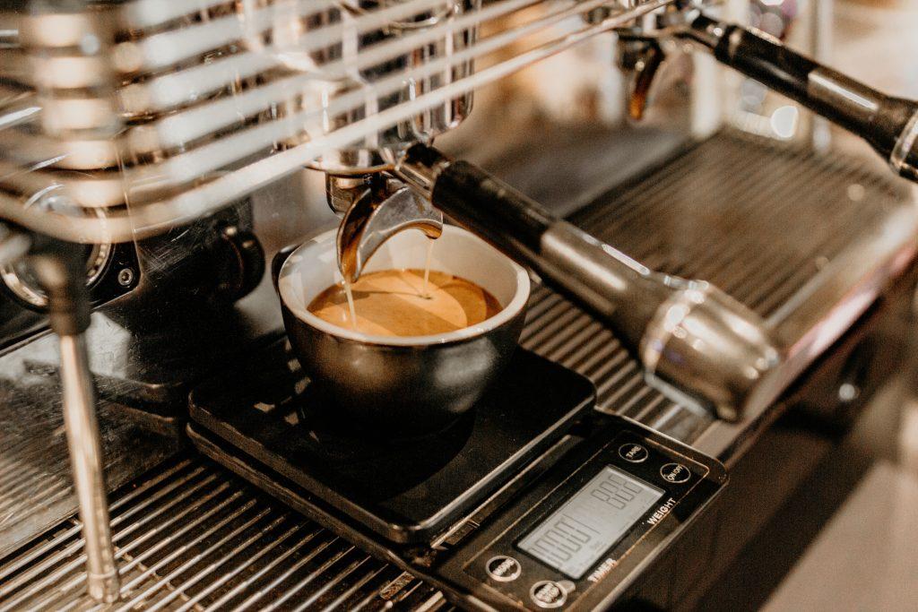 Na imagem há uma máquina de café despejando o café em uma xícara de cor preta e revestida na cor branca.