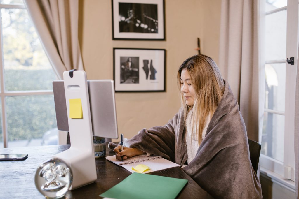 Na imagem há uma mulher de origem asiática sentada em uma cadeira, com um cobertor em torno de seu corpo e escrevendo em um caderno com uma caneta enquanto acompanha algo que está sendo visto pela tela de um computador.