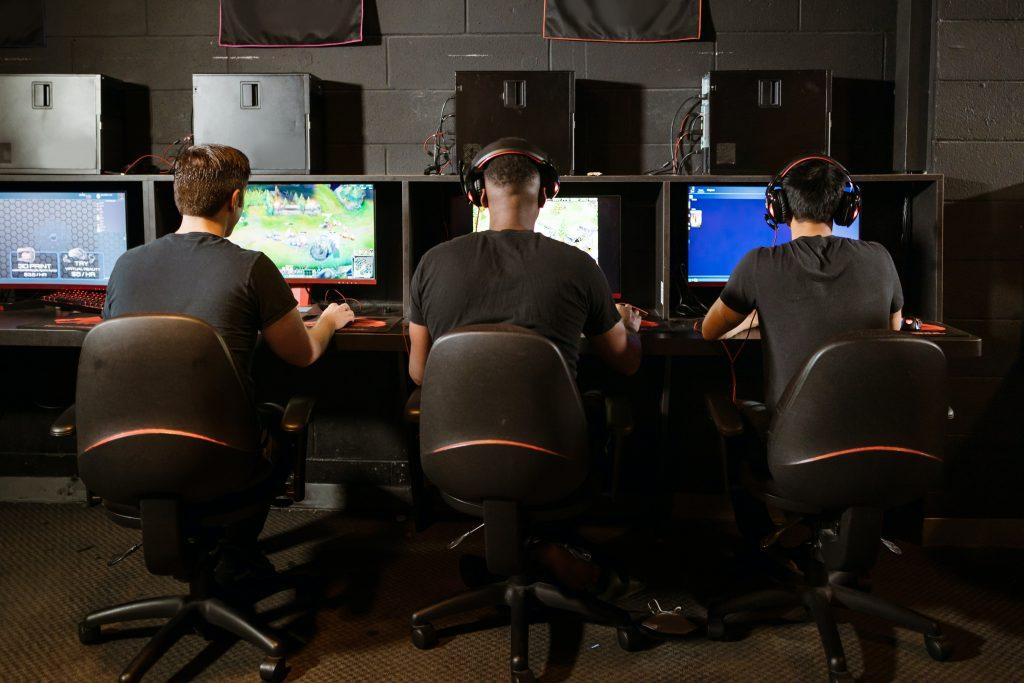 Na imagem há três pessoas sentadas em cadeiras, jogando uma das categorias de e-sports.