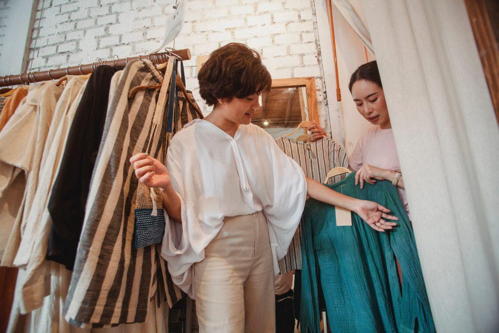 Na imagem há duas mulheres caucasianas, sendo que uma delas está segurando dois cabides com dois tipos de blusas diferentes enquanto a outra mulher está escolhendo qual das blusas ela gostou.