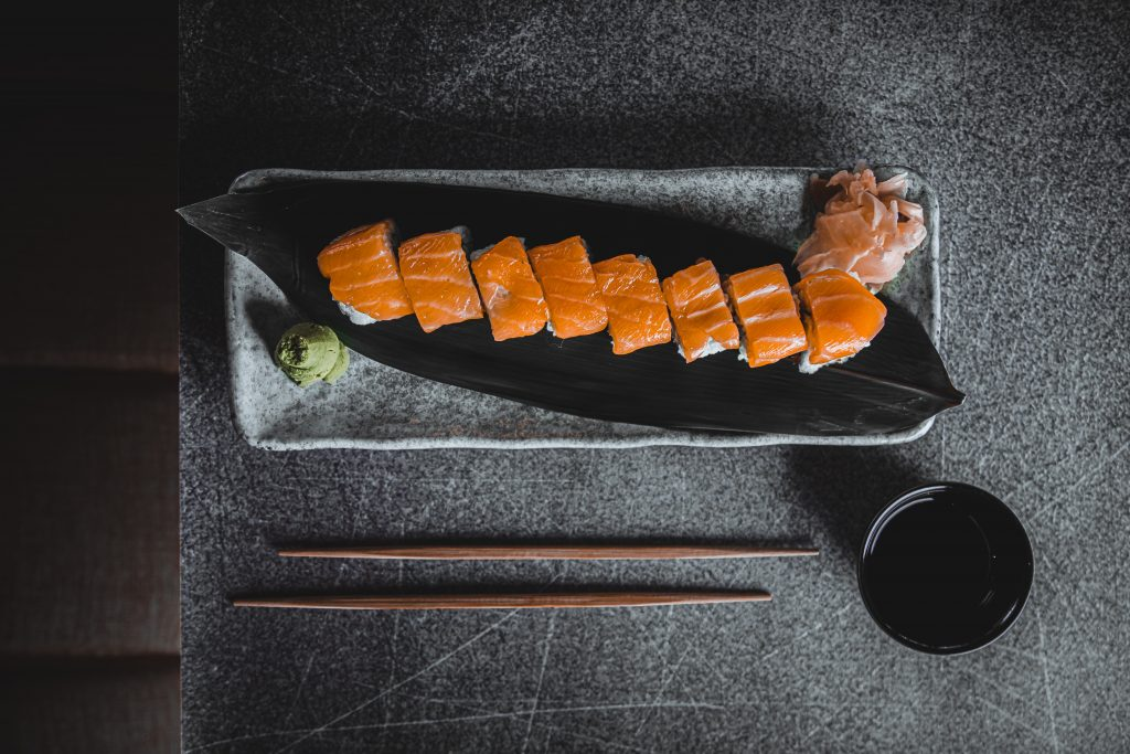 Na imagem há um prato retangular com uma fileira de sashimi sobre uma bancada. Próximo ao prato há 2 hashi e uma cumbuca preta com shoyo.