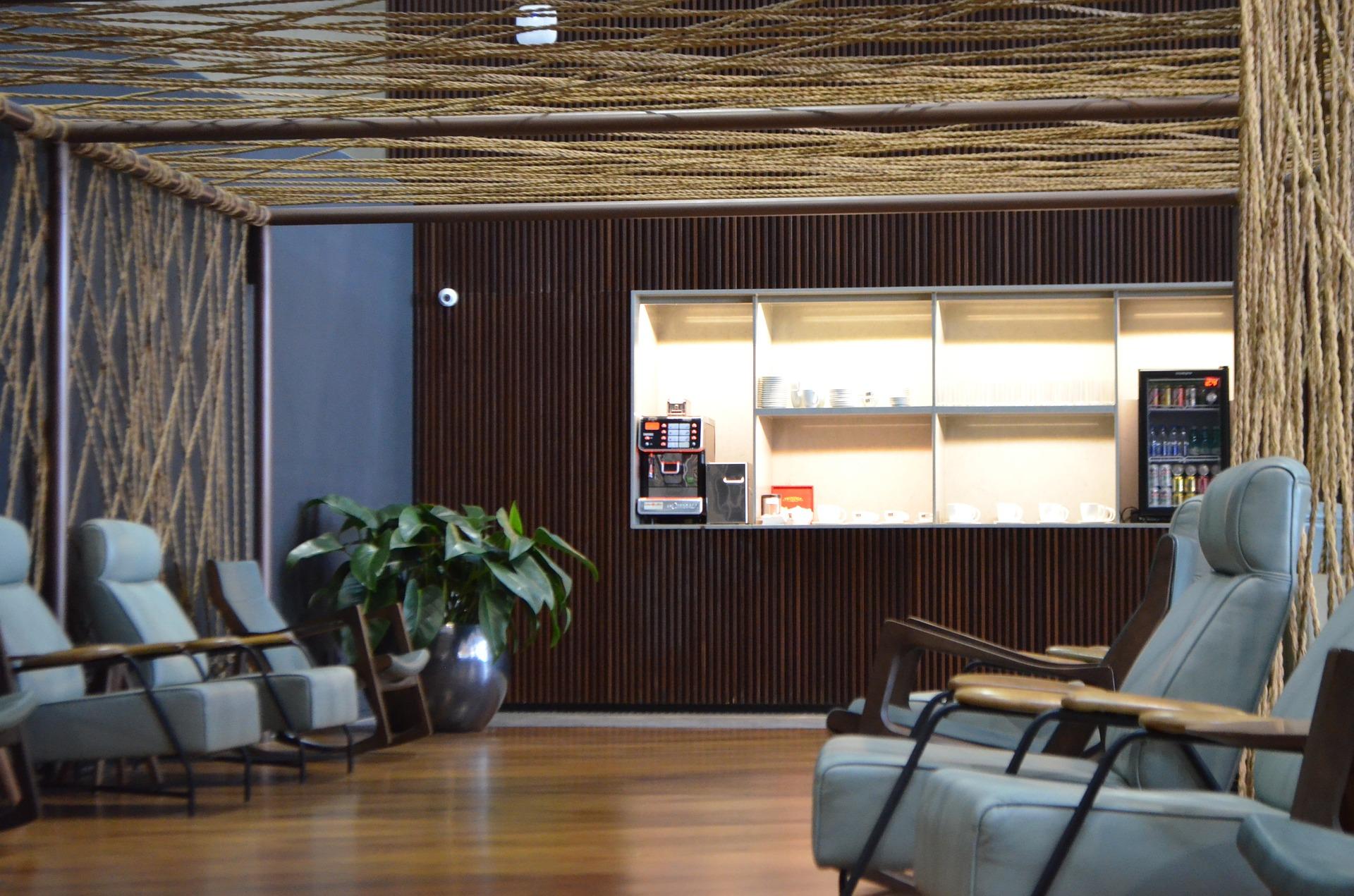 Na imagem há uma sala com poltronas de cores cinzas, um local para consumo de bebidas geladas e quentes e um vaso com plantas no canto esquerdo da imagem.
