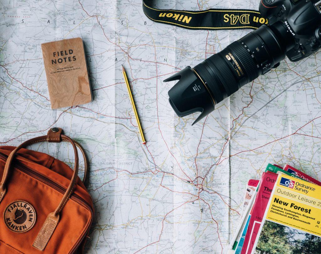 Na imagem vemos um mapa e, sobre ele, uma máquina fotográfica preta grande, uma bolsa marrom, revistas de turismo, um lápis grafite amarelo e um bloco de notas marrom.