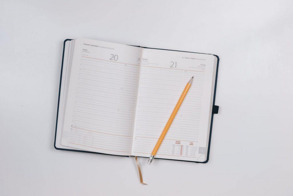 Na imagem temos uma agenda preta aberta nos dias 20 e 21. Além disso, em cima da agenda, há um lápis grafite amarelo.