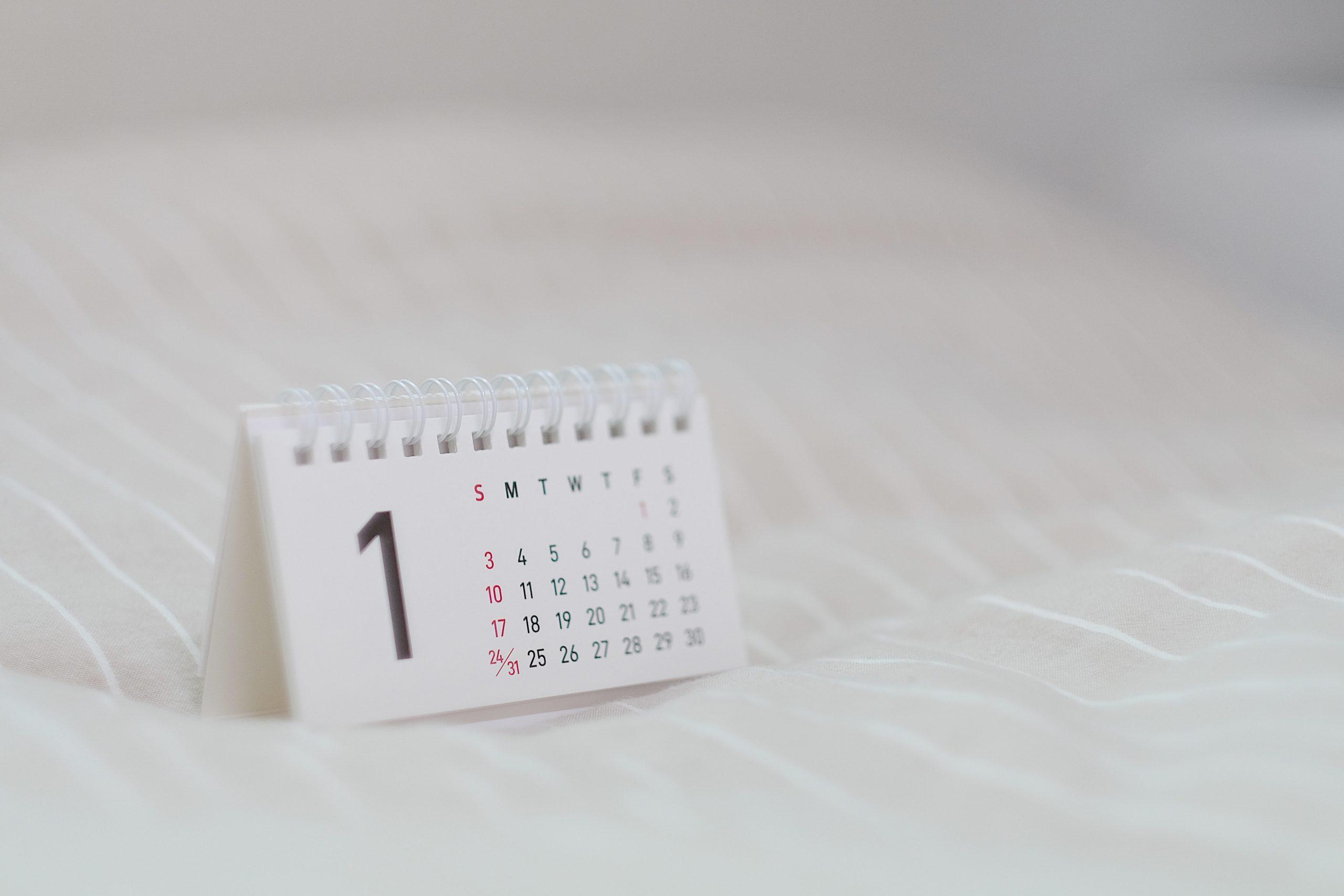 Na imagem existe um calendário pequeno em cima de uma superfície macia. No calendário, o número 1 está em destaque.