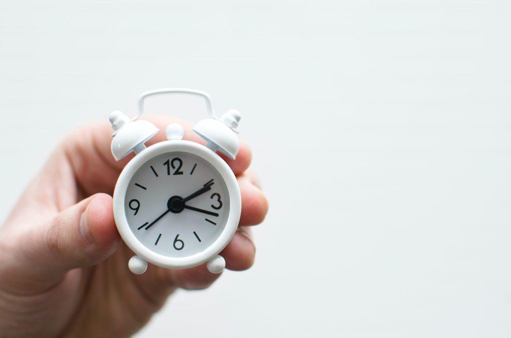 Na imagem uma mão segura um relógio pequeno branco com ponteiros e números pretos.Na imagem uma mão segura um relógio pequeno branco com ponteiros e números pretos.