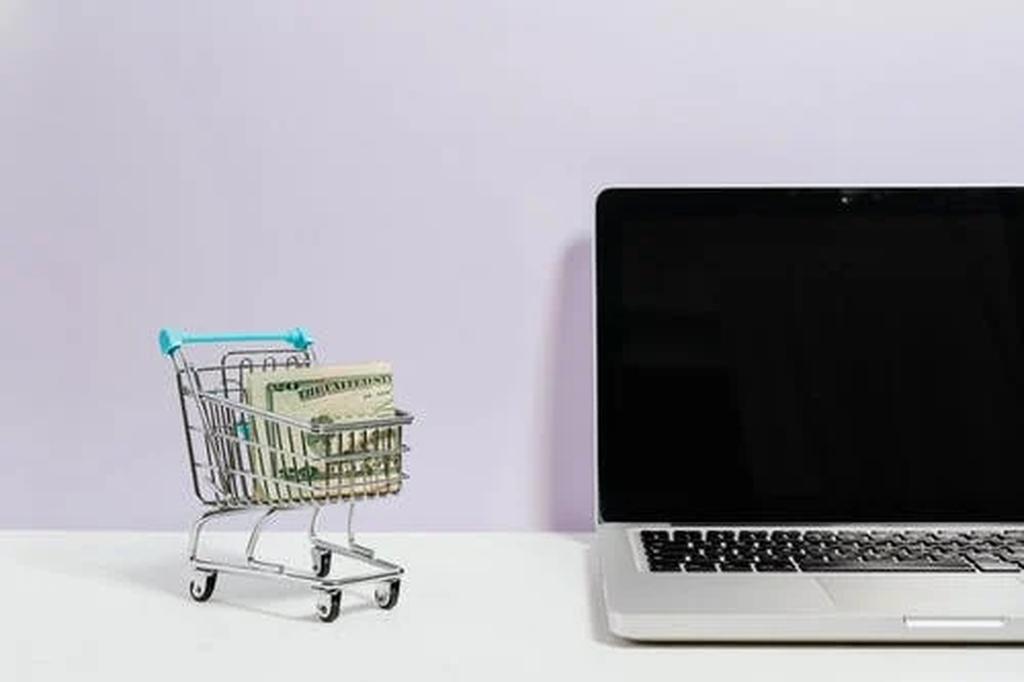 Notebook aberto em um fundo branco em cima de uma superfície branca. Ao seu lado esquerdo uma miniatura de carrinho de supermercado com notas de dinheiro dentro dele.