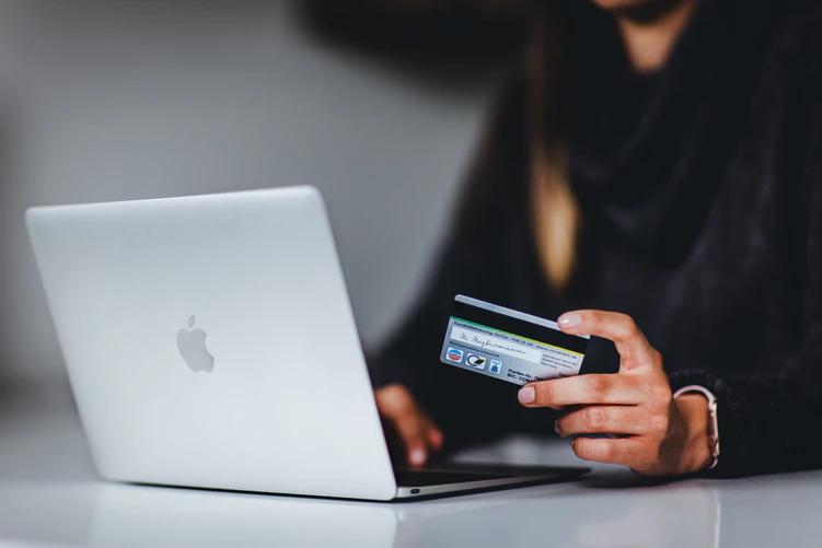 Mulher de blusa preta segurando seu cartão de crédito enquanto mexe em um notebook que está em cima de uma mesa branca.