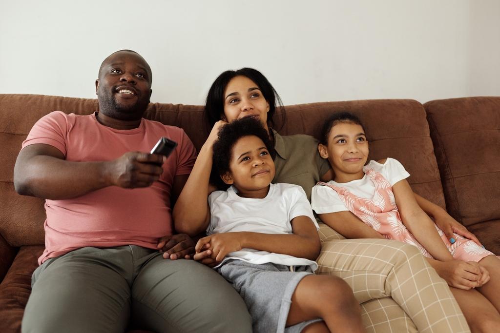 Família composta por um homem, uma mulher e duas crianças, sendo um garoto e uma garota sentados em um sofá marrom. O homem tem um controle remoto na mão e pela expressão facial a família está assistindo televisão.