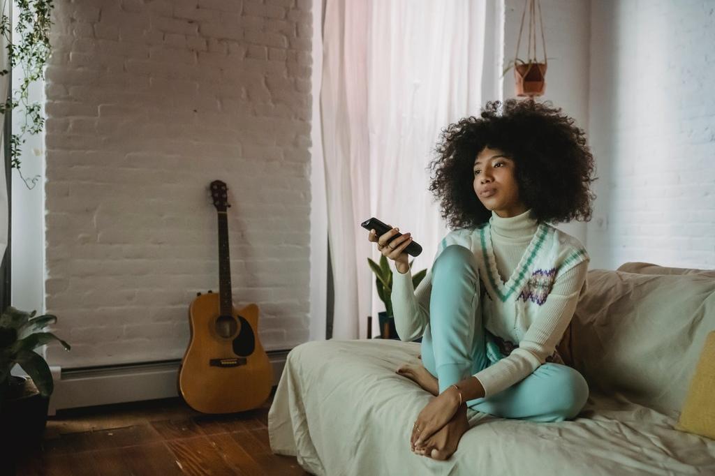 Mulher de blusa branca, colete de lã e calça azul, segurando um controle remoto, sentada em um sofá bege. Ao fundo, temos paredes de tijolinho branco, uma janela com cortina branca, algumas plantas e um violão.