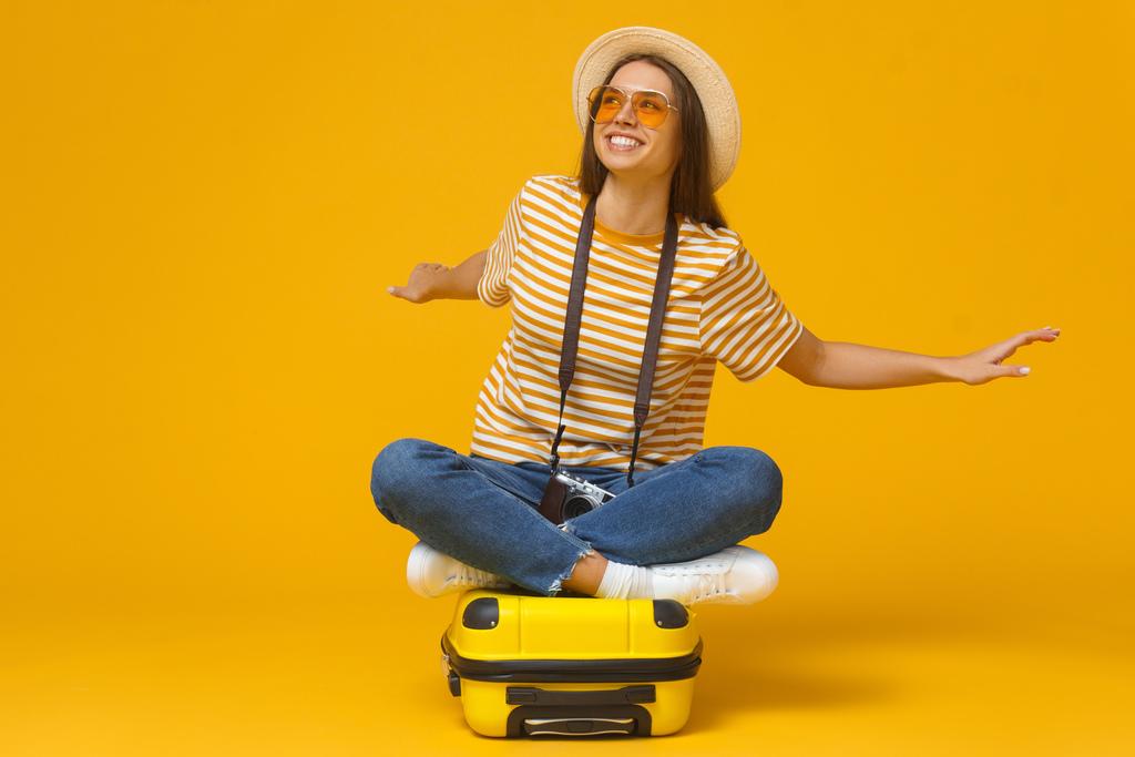 Imagem de fundo amarelo composta por uma mala amarela na qual uma mulher de calça jeans, camiseta listrada amarela, óculos de sol amarelo, chapéu e uma máquina fotográfica no pescoço, está sentada com os braços abertos e expressão facial de alegria