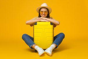 Imagem de fundo amarelo composta por uma mala amarela na qual uma mulher de calça jeans, camiseta listrada amarela, óculos de sol amarelo, chapéu e uma máquina fotográfica no pescoço, está abraçada com uma expressão facial de alegria
