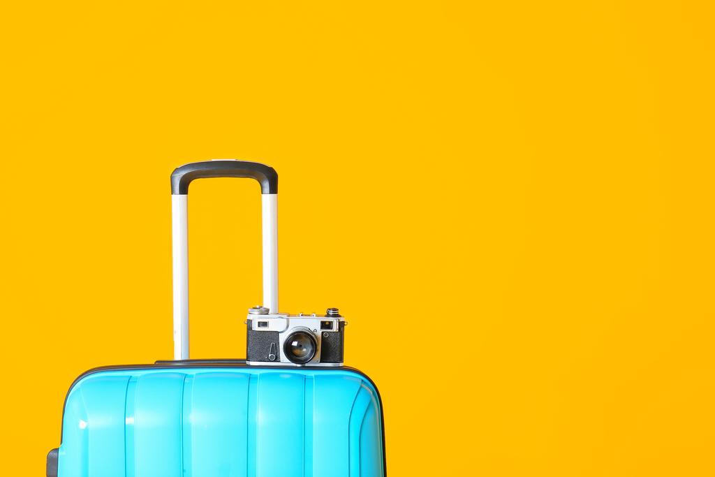 Imagem de fundo amarelo composta por uma mala azul com uma máquina fotográfica em cima