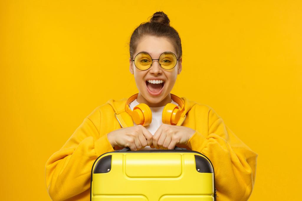 Imagem de fundo amarelo composta por mulher de camiseta branca, jaqueta amarela, fone de ouvido amarelo e óculos de sol amarelo segurando uma mala amarela com uma expressão facial de alegria