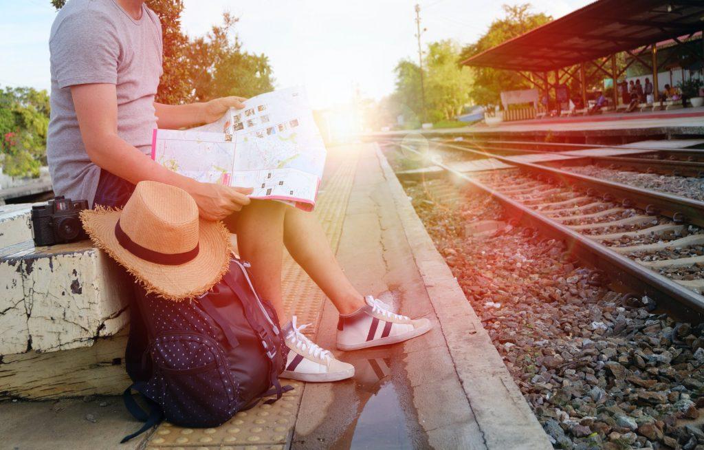Homem sentado em uma pedra segurando um mapa ao lado de uma linha de trem. Ao seu lado uma câmera fotográfica, uma mochila e um chapéu.