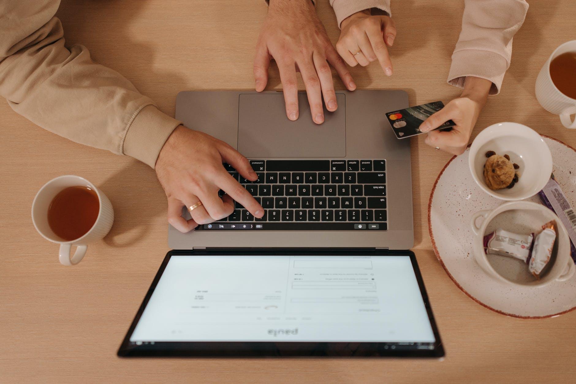 Notebook sobre mesa de madeira, ao lado algumas xícaras, duas pessoas manuseando o notebook, uma delas com um cartão de crédito nas mãos.