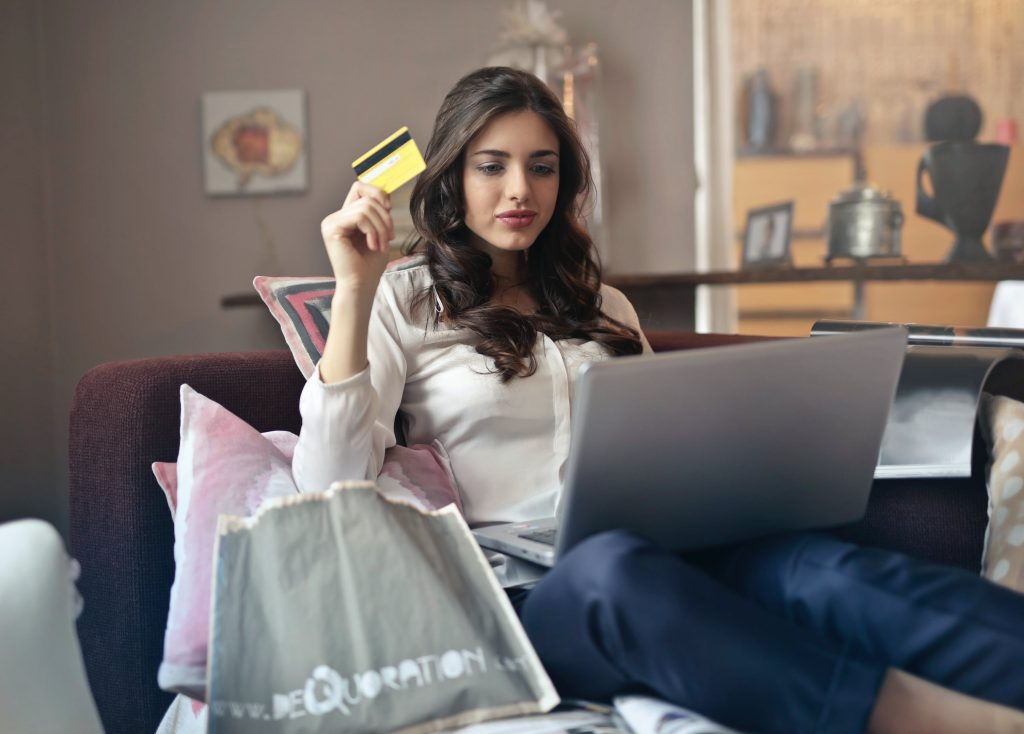 Mulher sentada em um sofá segurando um cartão com um notebook no colo. Ao seu lado vemos almofadas e sacolas de compra.