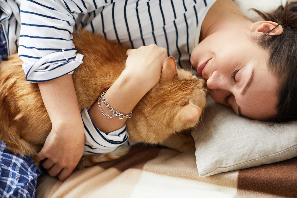 Mulher de blusa listrada deitada em uma cama abraçada com um gato laranja